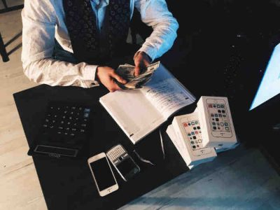 man at desk counting money with a notebook open