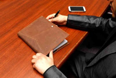 desk with a man hands and notebook with a pen in his hand